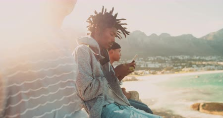 african decent : African American looks at smartphone and sits outside while mixed race friend sits beside him at the seaside during sunset