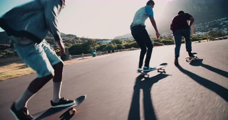 teen action : Multi-Ethnic group of skater friends skateboarding down road at seaside together during sunset