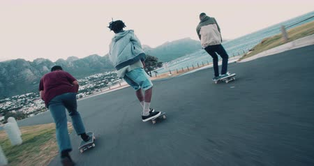 african decent : Multi-Ethnic group of skater friends skating down street along seaside Stock Footage
