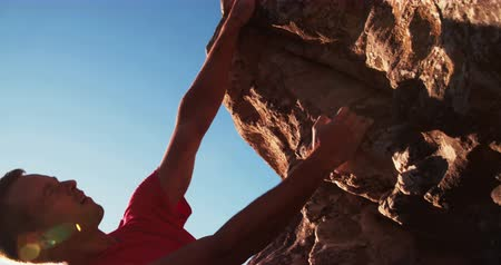 alpinista : Low angle of experienced rock climber hanging on rock with sunflare