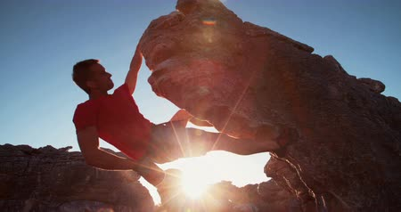 alpinista : Bouldering climber man puts hand into bag full of chalk for grip while climbing rock wall on mountain at sunset or sunrise.
