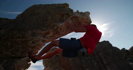 wspinaczka : Rock climber holding on to rock overhang as he boulders up mountain. He is strong and focused. Wideo