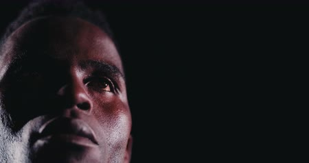 african decent : A close up of face of an African american basketball player looking straight forward with defiant expression in the dark with one court light source Stock Footage