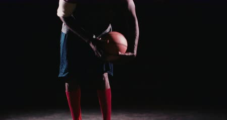 african decent : African American basketball player with feet on ground and touching ball on court ground in night with single light source Stock Footage