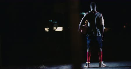 african decent : Full body shot of African American basketball player standing with back towards camera holding basketball on hip with arm in court with one single court light source