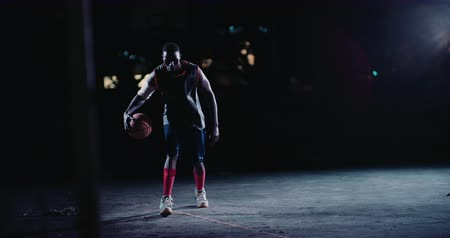 african decent : African American basketball player runs forward while bouncing ball on court in the night with single court light source