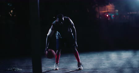 african decent : African American basketball player crouched down and dribbling ball alone lit by one court light source