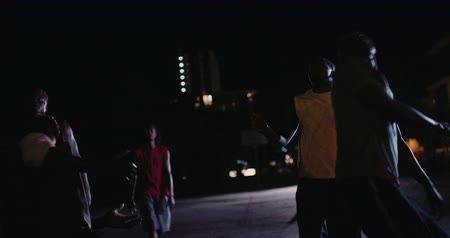 african decent : Low shot of African American basketball players playing in inner-city court during nighttime with single light in background Stock Footage