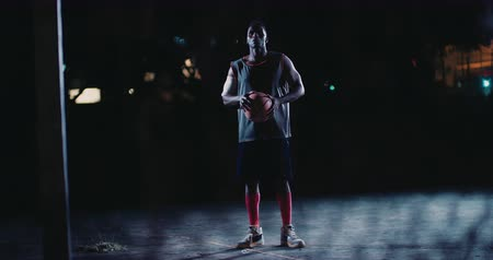 african decent : African American urban basketball player holds ball in his hands in a street light lit inner-city basketball court