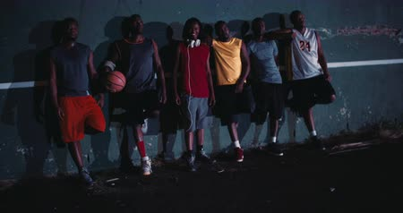 etnisite : Group of African American basketball players lined up against black court wall in the night with spot light source fixed on them