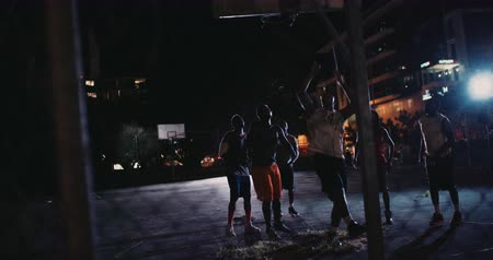 african decent : African American basketball players watch ball go into basket in inner-city court during nighttime with single light in background Stock Footage