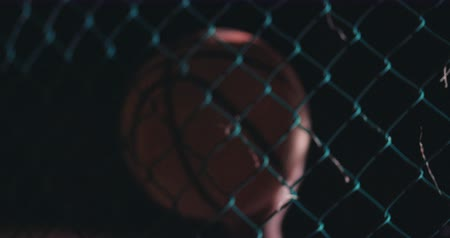 fárasztó : African American basketball player standing at court fence, holding ball against hip in the night with lights in background