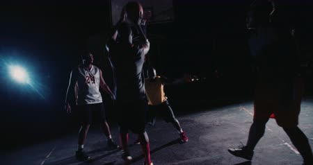 african decent : African American basketball players playing in inner-city court during nighttime with single light in background