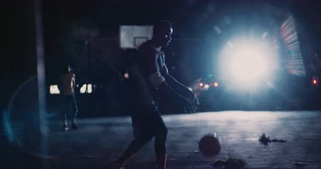 african decent : African American male basketball player is practicing moves and shooting a basket alone in an empty court at night with lights in background Stock Footage