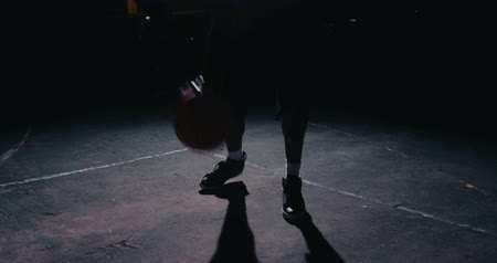 баскетбол : Male urban basketball player dribbles ball in crouched position in an inner-city basketball court lit by single street light