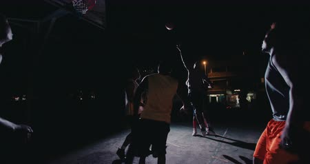 african decent : African American basketball players playing in inner-city court with man throwing ball into basket during nighttime with single light in background