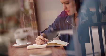журнал : Brunette Woman sitting and writing in her journal on wooden counter top window seat in busy coffee shop