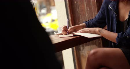 yazarak : Hipster Brunette Woman sitting and writing in her journal on wooden counter top window seat in busy coffee shop Stok Video