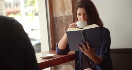 coffee time : A brunette caucasian woman sits at window seat of coffee shop, drinking coffee and reading a book Stock Footage
