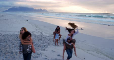 Калифорния : Aerial View of a Group of hipster friends having fun doing piggyback rides on beach at sunset on summertime