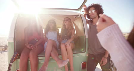 hipster : Hipster Multi-Ethnic Group sit in back of open retro van parked at a sandy beach