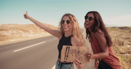 hippi : Caucasian Hipster girl and African American hipster girl in the daytime stand on side of two lane highway hitchhiking while holding cardboard sign with the word Happiness written on it and sticking out thumb Stock mozgókép