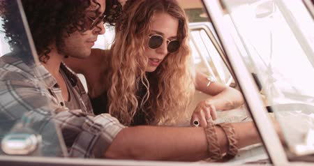 hippi : Window perspective of Hipster mixed race man and hipster caucasian woman holding open a map and looking at it in the front seat of a retro van Stock mozgókép