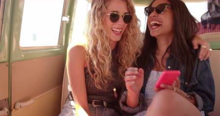 gravado : Boho or hipster fashion woman laughing out loud looking at her smart phone with mixed race girl friend in vintage van during a road trip. Stock Footage