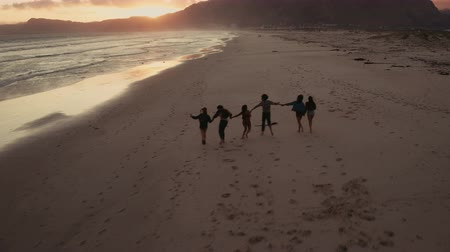 regenerating : Young adult female friends enjoying a regenerating walk at beach on sunset. Aerial view from drone flying over.