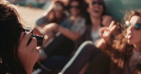 hipster : Hipster multi-ethnical friends showing peace sign, posing and making funny faces while a friend of theirs is taking a picture outside at sunset during their van road trip Stock Footage