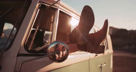 utazó : Young woman relaxing by crossing legs out of the window of a nice vintage van on sunset
