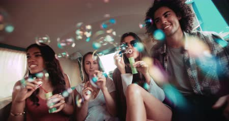 amigos : Group of multi-ethnical hipster friends having fun with soap bubbles inside a vintage van to celebrate their road trip Vídeos