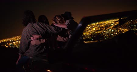 arka görünüm : Back view of a group of friends hugging sitting on the bonnet of a car and watching night city lights from viewpoint Stok Video