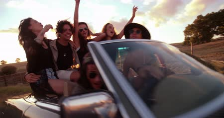 utazó : Group of teenager friends celebrating their road trip on a vintage convertible car hugging joyously with sunset sun flare