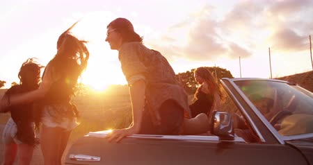 смеющийся : Portrait of multi-ethnic teenager friends in hipster style smiling and dancing outside with summer sun flare