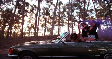 utazó : Group of teenager friends celebrating their road trip on a convertible car with smoke bombs on a sunny summer afternoon