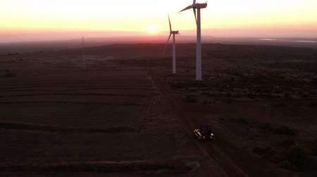 viagem por estrada : Group of friends reaching a wind farm in California with a vintage convertible car on a summer road trip Stock Footage