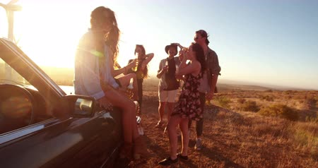 na zdraví : Group of friends toasting with beer outdoor on a summer sunset evening during their vintage convertible road trip Dostupné videozáznamy