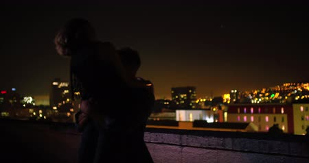 tetőtéri : Man is holding hand with girlfriend who is balancing on rooftop edge with city lights in background at night