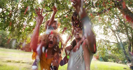 izgatott : Young attractive african-american family playing together in picturesque park throwing confetti in the air and laughing happily Stock mozgókép