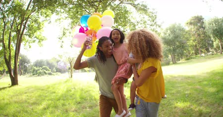 yazlık : Cheerful african-american couple carrying their beautiful daughter and son  with colourful heliumballoons in hand at a beautiful summery park.