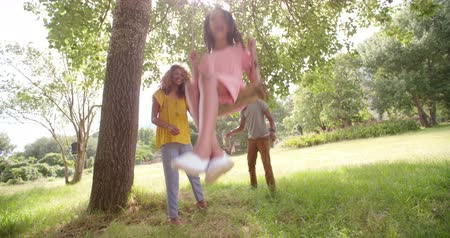 houpavý : Sweet African-American girl laughs while her mom and dad pushes her on the swing hanging on a stunning tree. Dostupné videozáznamy