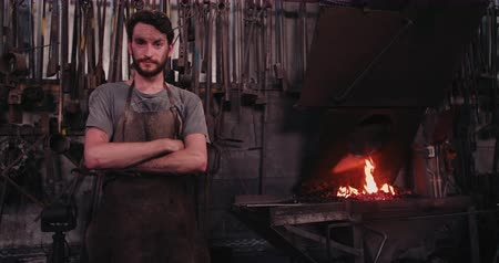 artesão : Portrait of a fulfilled young adult craftsman standing in his blacksmith factory Vídeos