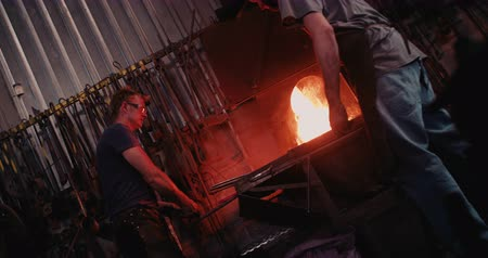 kowal : Two blacksmith working in metal industry forging iron at furnace in Slow Motion
