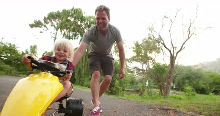 toló : Cheerful father pushing his laughing child in a yellow toy pedal car on the road