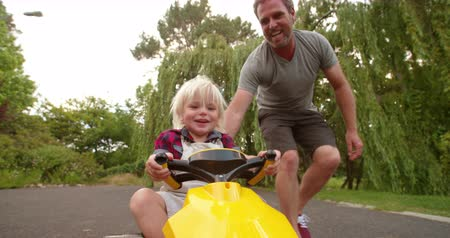 despreocupado : Cheerful father pushing his laughing child in a yellow toy pedal car on the road