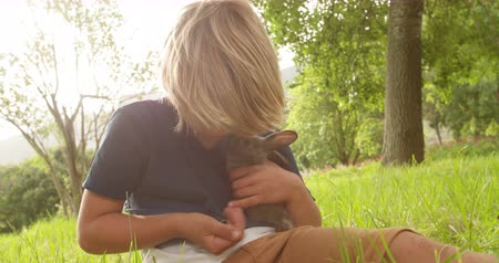 male animal : Happy elementary age blond boy takes a little bunny on his arms sitting at the park Stock Footage