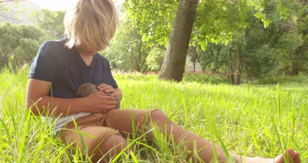 nyúl : Happy elementary age blond boy takes a little bunny on his arms sitting at the park Stock mozgókép