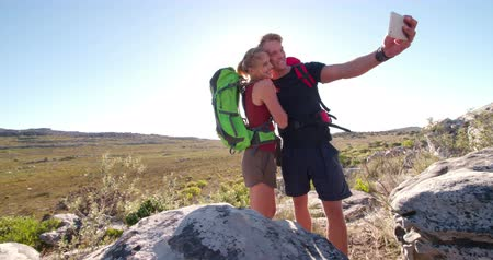 etkinlik : Fit couple looking happy at their camera for a selfie during outdoor hiking adventure