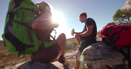 поход : Man drinking from water bottle while woman takes off backpack for the couple to rest on rock from hiking in summer sun Стоковые видеозаписи